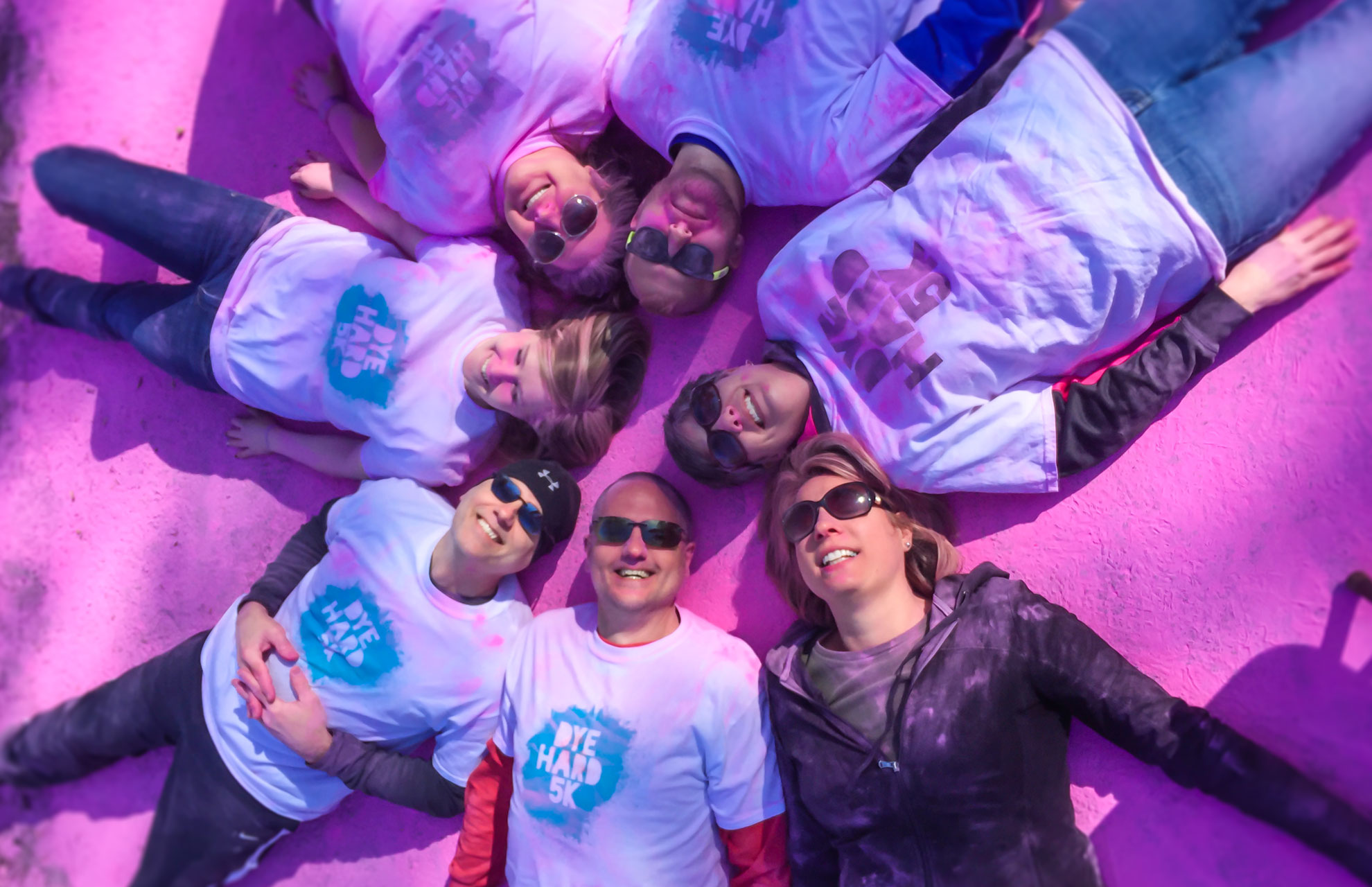 Holmes staff and family members laying on a dyed street after the Dye Hard 5K Color Run