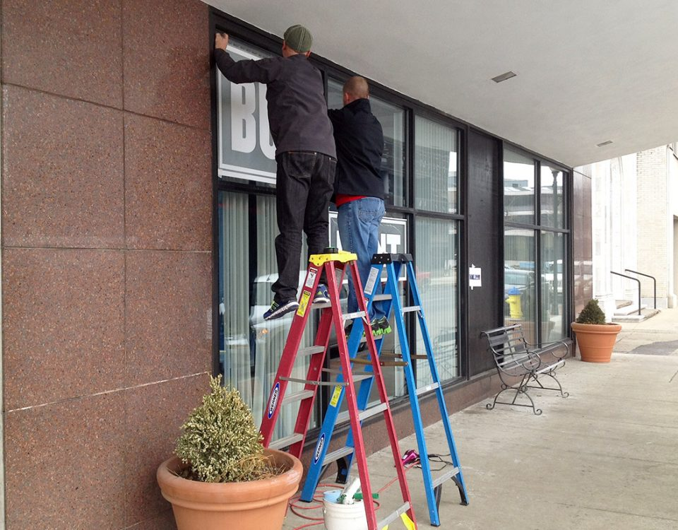 Brian Holmes installing a large format outdoor window graphic