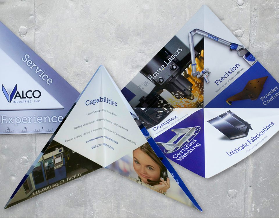 Multiple Views of a Custom Die-cut Brochure Designed for Valco Industries, Inc. on a metal background