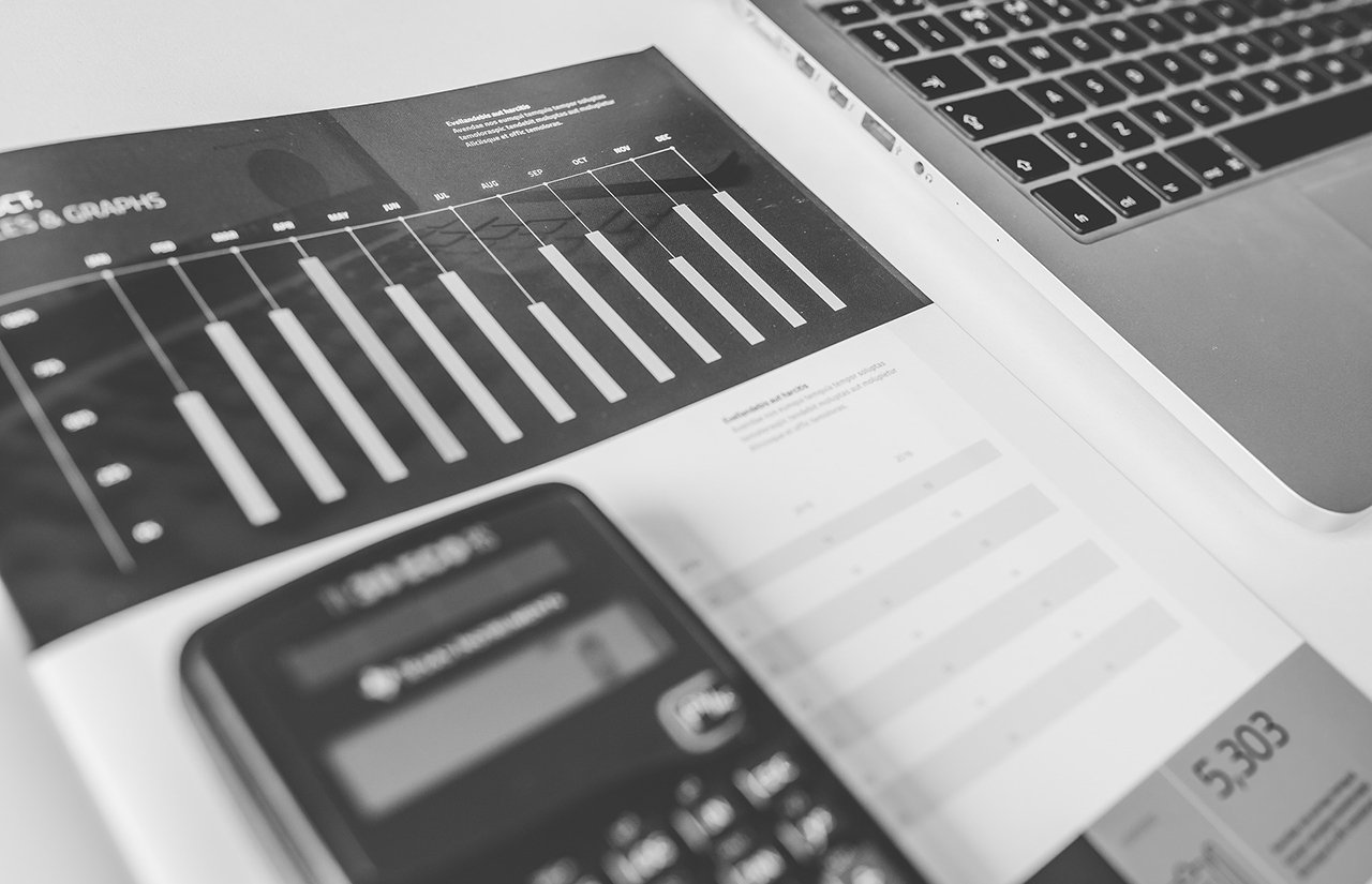 Calculator, bookkeeping, laptop shown in black and white