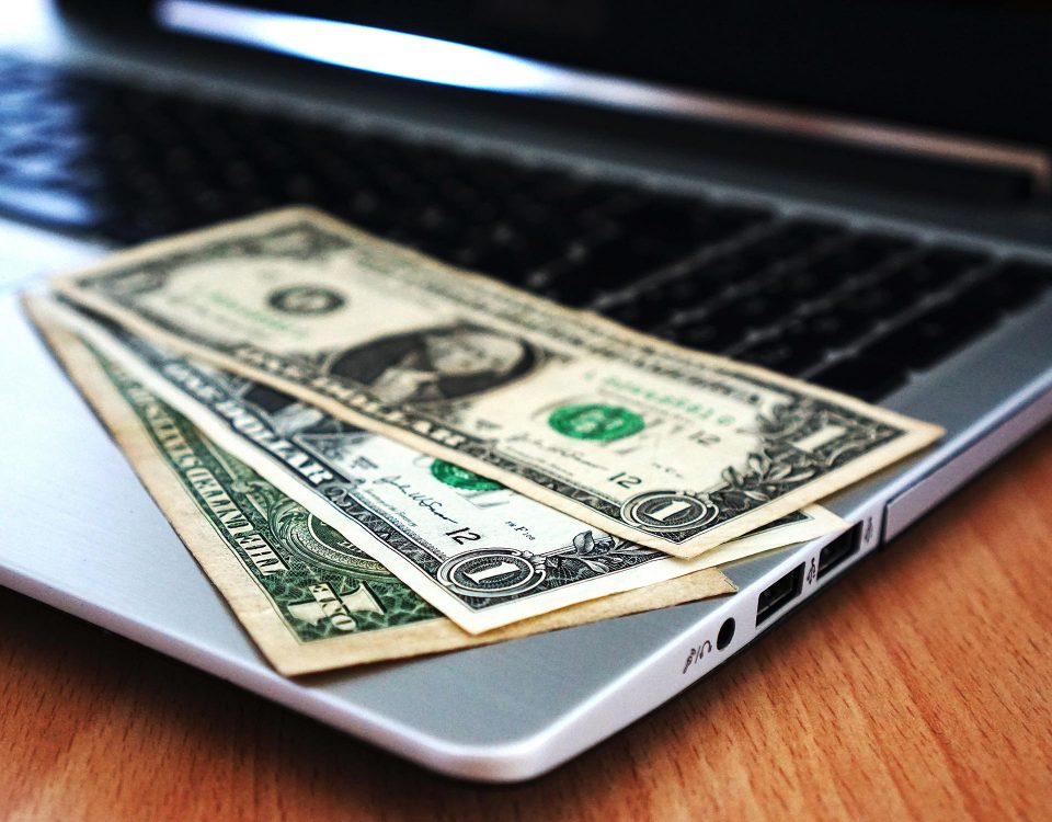 laptop with three one dollar bills on the keyboard