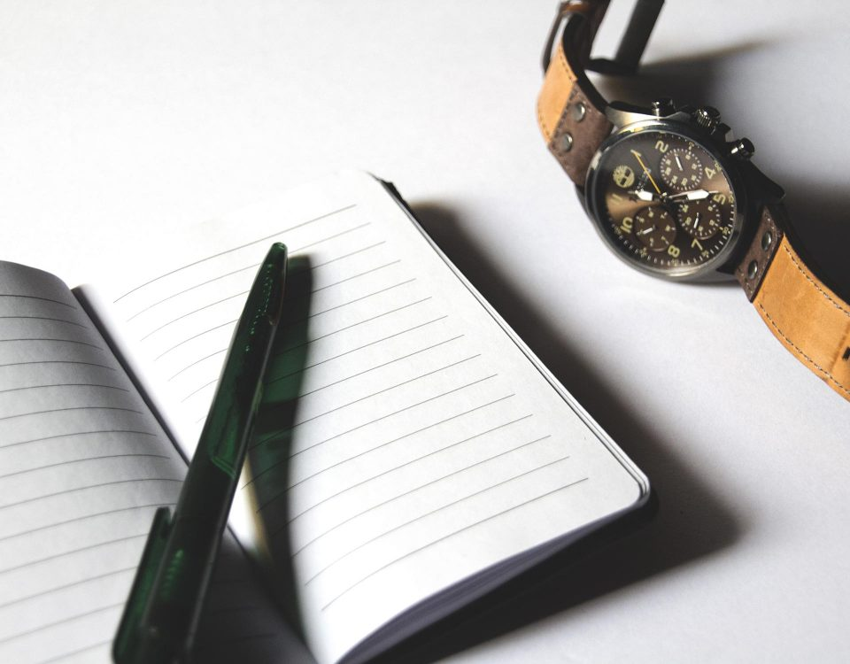 watch, pen, and notepad on white background