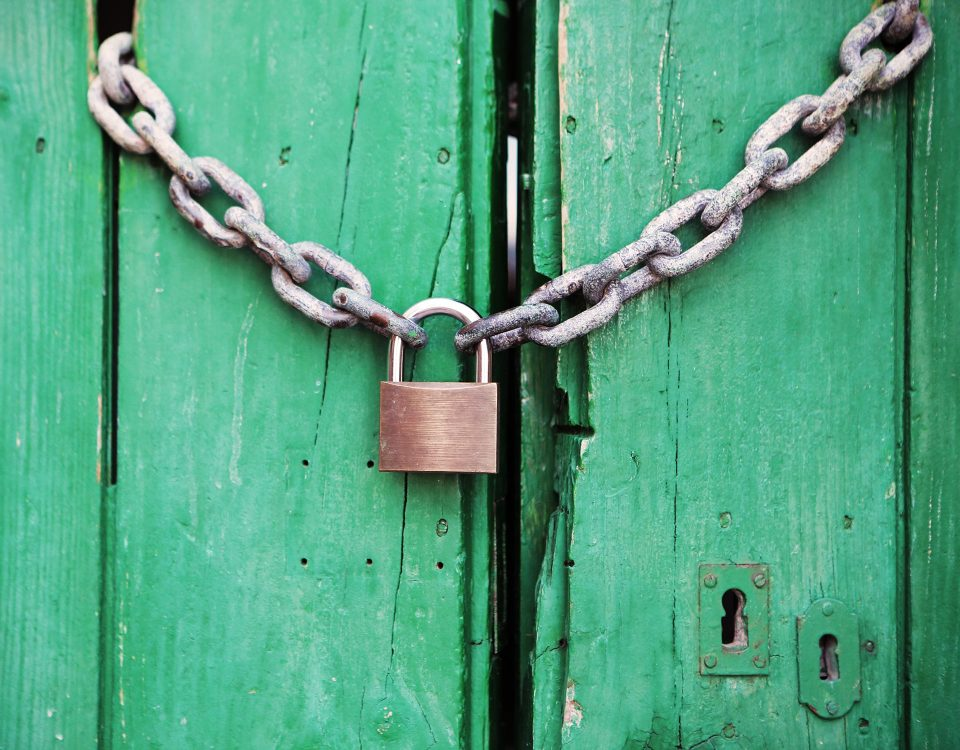 green door with chain and padlock on handles