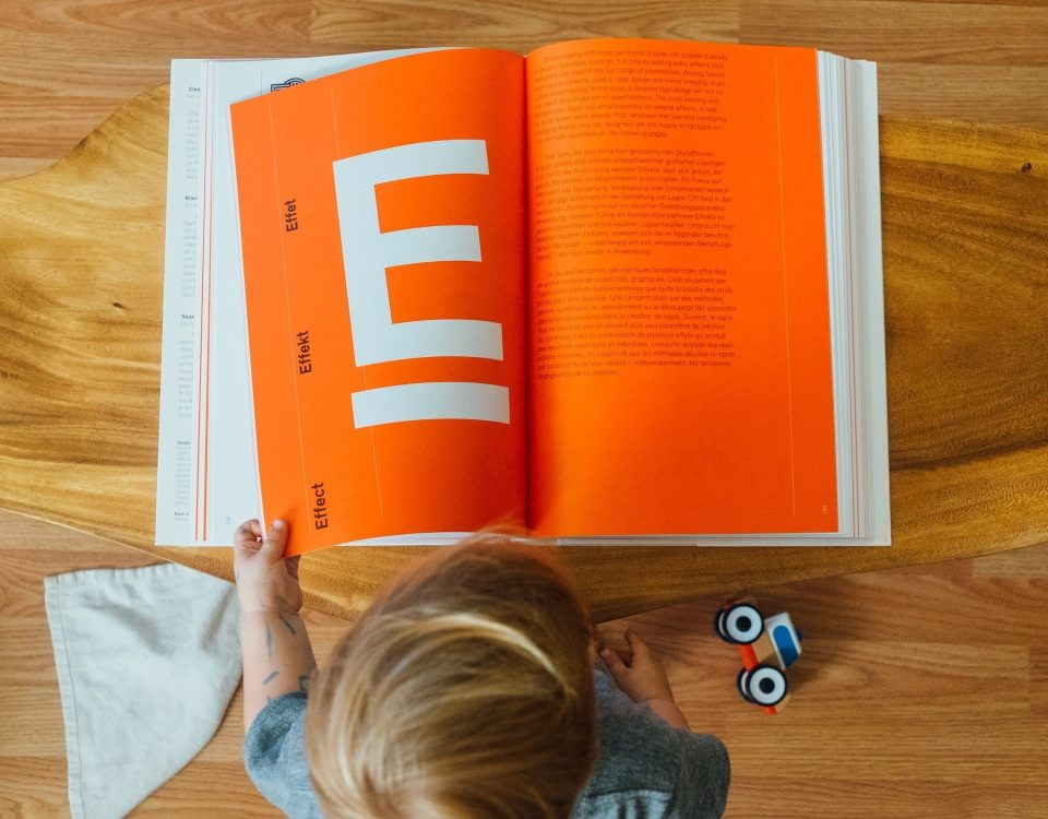 child looking through a book about graphic design